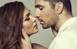 A man and a woman almost kissing. The Women's Health Specialists of Dallas doctors provide preventive care exams, STD testing, and treatments for HPV.