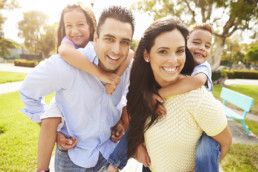 Caucasian family with father holding daughter on back and mother holding son on back