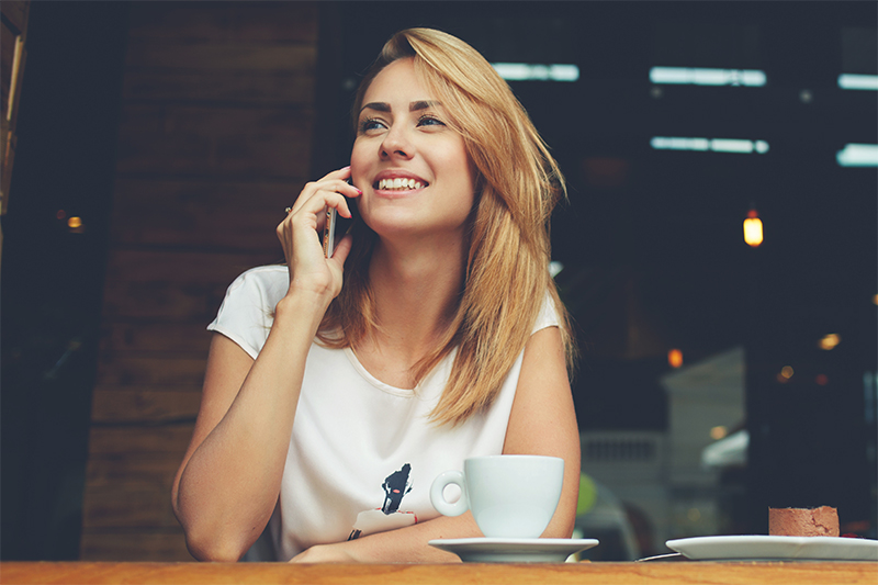 Caucasian woman sitting and speaking on a cell phone smiling