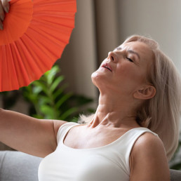 A woman suffering from a hot flash due to a Hormonal Imbalance