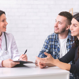 A couple and a physician discussing Infertility issues