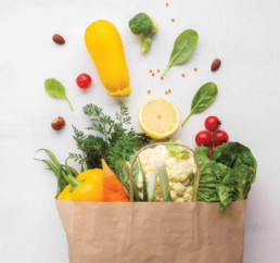 Large brown paper bag full of colorful vegetables